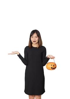 Портрет молодой женщины в костюме черной ведьмы держит тыкву на вечеринке happy halloween.