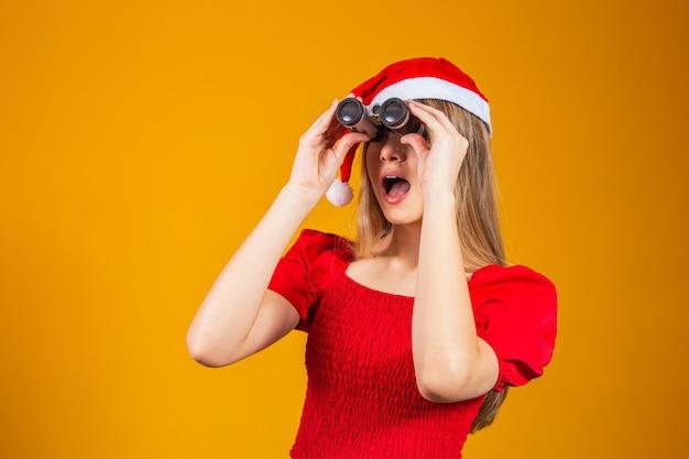 쌍안경을 통해 보고 크리스마스 옷을 입고 젊은 여자의 초상화