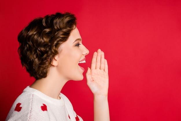Портрет молодой женщины в стильном модном джемпере, изолированном на красной стене