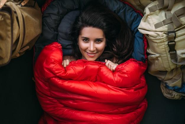 Портрет молодой женщины, уютной и теплой в красном спальнике. милая туристическая девушка с красным спальником в палатке. путешествие по лагерю, женщина отдыхает в спальнике. походы, отдых на природе
