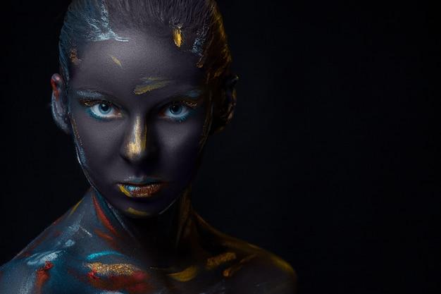 Портрет молодой женщины, которая позирует покрыта черной краской