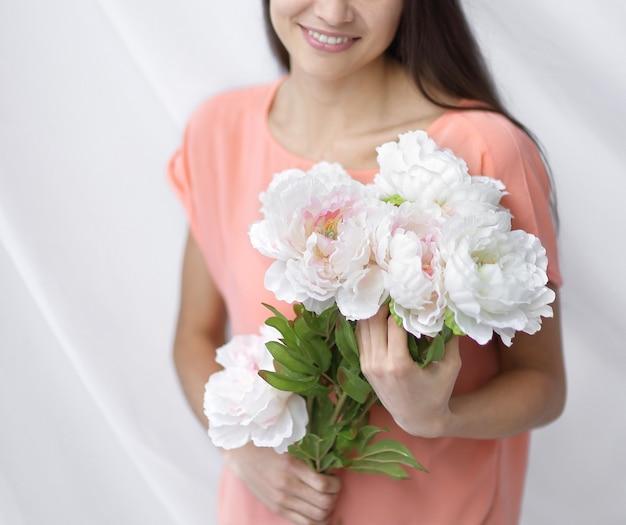 牡丹の花束を持つ若い女性の肖像画。