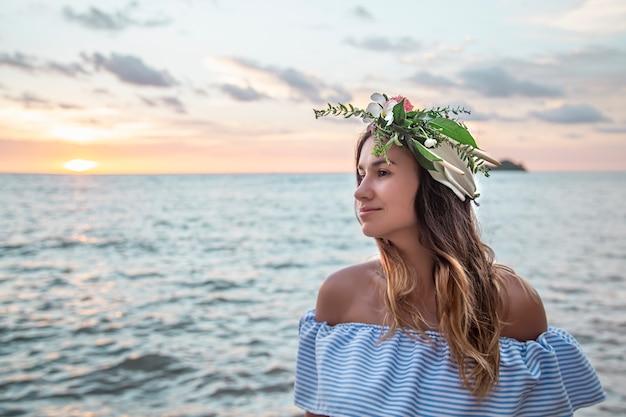석양 바다에 대 한 그녀의 머리에 꽃의 성분과 젊은 여자의 초상화.