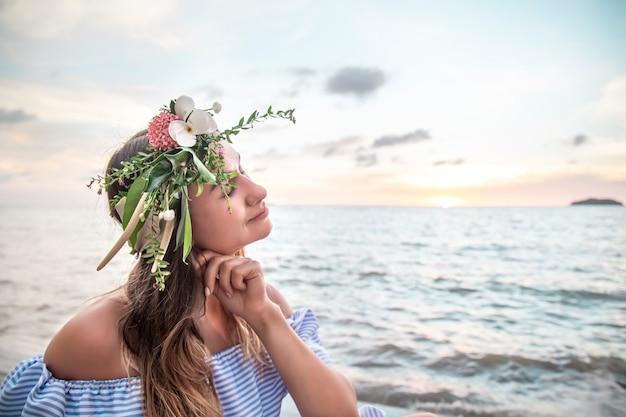 석양 바다에 의해 그녀의 머리에 꽃의 성분과 젊은 여자의 초상화.