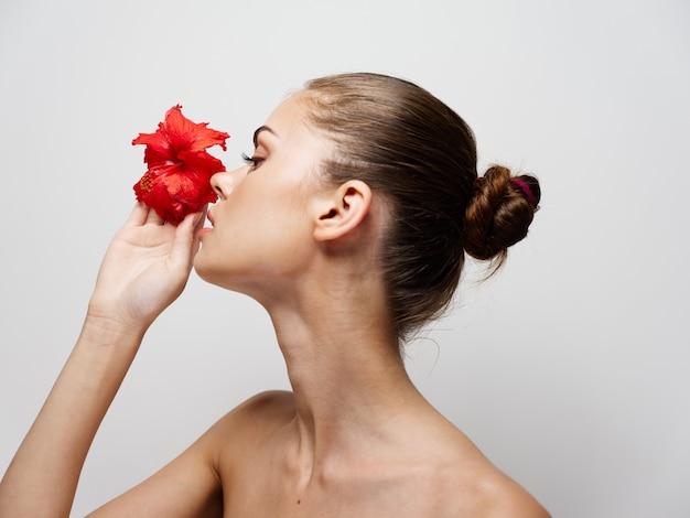 明るい背景のきれいな肌の美容に彼女の手に花を持つ若い女性の肖像画