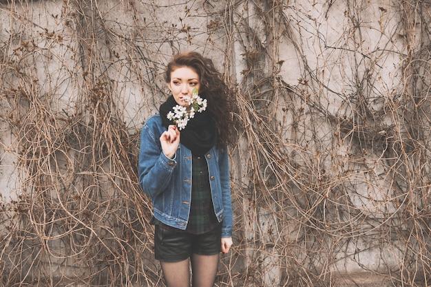 都市公園に立っているライラックの枝を持つ若い女性の肖像画