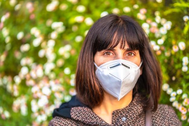 아름 다운 데이지 옆에 마스크와 젊은 여자의 초상화. 통제되지 않은 covid-19 전염병의 첫 걸음