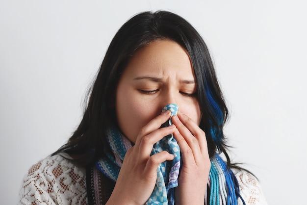 ハンカチを使用して鼻水を持つ若い女性の肖像画