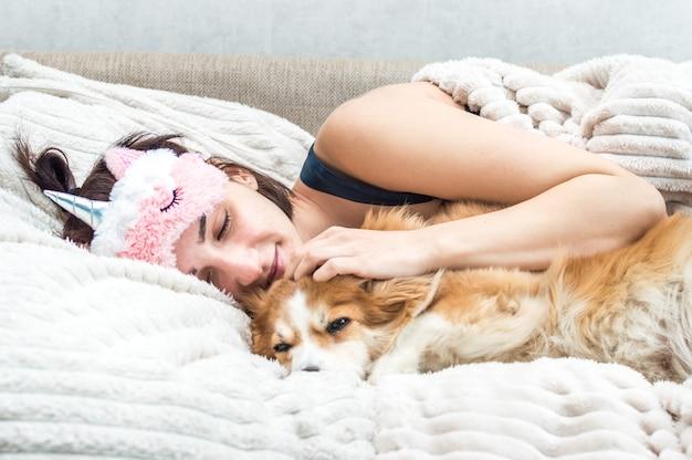 수면 마스크와 잠옷을 입고 개를 껴안고 있는 젊은 여성의 초상화. 휴식과 수면의 개념입니다.