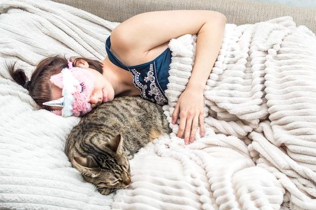 얼굴에 수면 마스크를 쓰고 고양이를 안고 잠자는 잠옷을 입은 젊은 여성의 초상화. 휴식과 수면의 개념입니다.