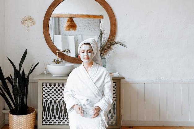 Портрет молодой женщины с белым халатом и полотенцем на голове. девушка позирует в ванной с маской из органической глины на лице.