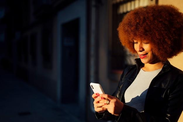日没時にダウンタウンの街の通りでスマートフォンを手にアフロヘアーの若い女性の肖像画-彼女のスマートフォンとミレニアル世代