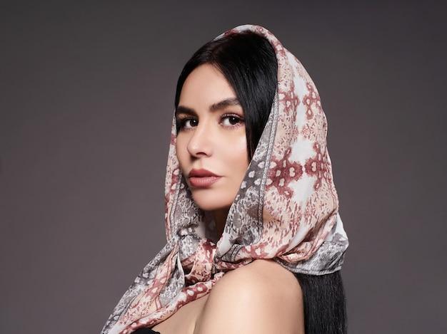 明るいメイクとファッショナブルなスカーフを持つ若い女性の肖像画。灰色の背景。美容、ファッション。