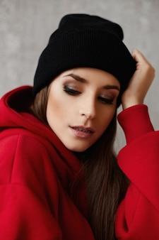 Портрет молодой женщины с ярким макияжем в черной шляпе и красной толстовке с капюшоном