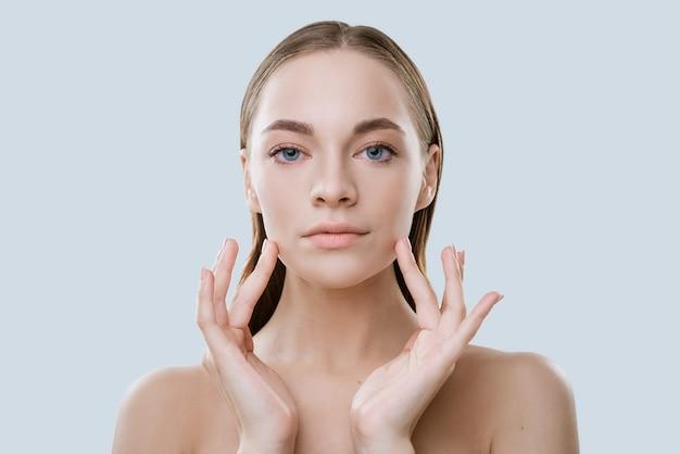 Портрет молодой женщины с чистой кожей касается лица пальцами на светлом фоне
