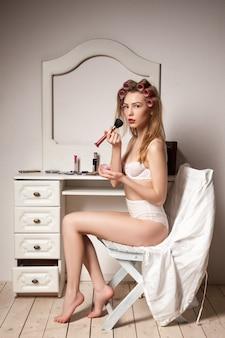 거울 뒤에서 화장을 하는 경기자 머리를 한 젊은 여성의 초상화