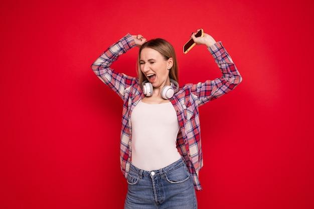 Портрет молодой женщины с наушниками и телефоном на красном фоне