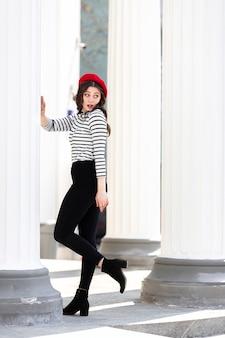 街の背景に赤いベレー帽の長い黒髪の若い女性の肖像画。