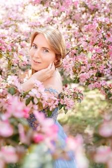 봄 공원 알레르기가 없는 개념의 꿈꾸는 소녀의 체리 장미 정원 배경에 붉은 머리를 한 자연스러운 흰색 피부를 가진 젊은 여성의 초상화