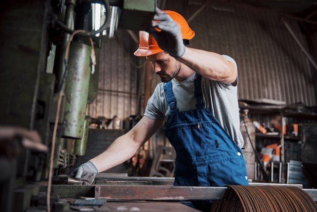 大規模な金属加工工場でヘルメットをかぶった若い労働者の肖像画。