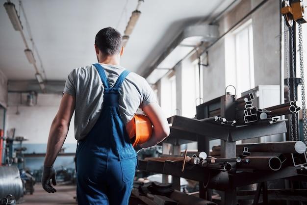 大規模な廃棄物リサイクル工場でヘルメットをかぶった若い労働者の肖像画。