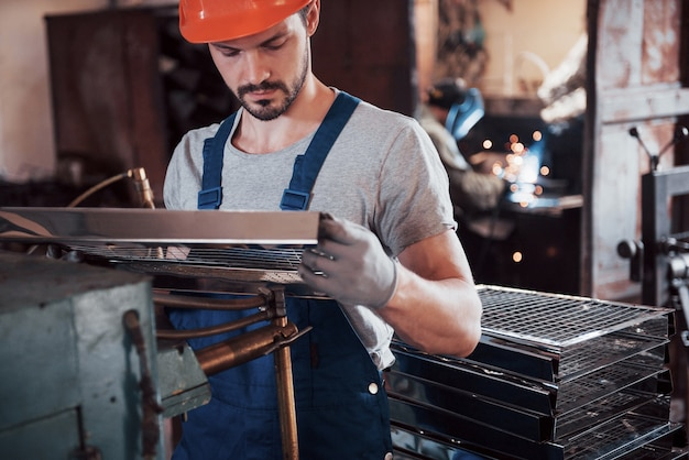 대형 폐기물 재활용 공장에서 하드 모자에 젊은 노동자의 초상화.