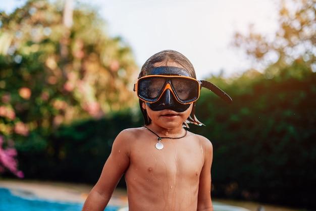 낮에는 고글을 쓰고 수영장 주변에서 포즈를 취한 젊고 젖은 어린 소년의 초상화.