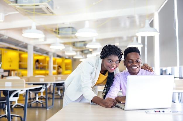 Портрет молодой черной женщины и парня, улыбающегося в рабочей среде с ноутбуками, африканского бизнесмена или студента
