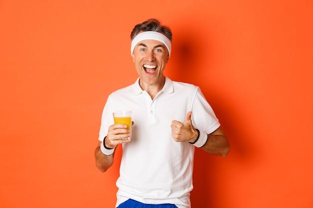 Портрет активного и здорового спортивного парня средних лет, показывает палец вверх