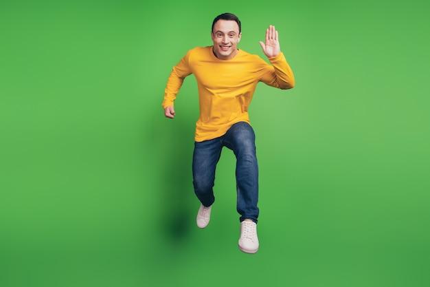 緑の背景にアクティブな陽気な男のジャンプラン波手挨拶友人の肖像画