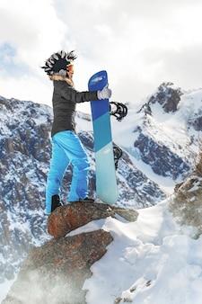 산 배경 위에 서 있는 재미있는 모자를 쓴 활동적인 여성 스노보더의 초상화