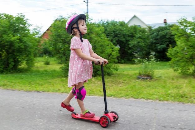 夏の日に村の道路でスクーターに乗ってアクティブな小さな幼児の女の子の肖像画