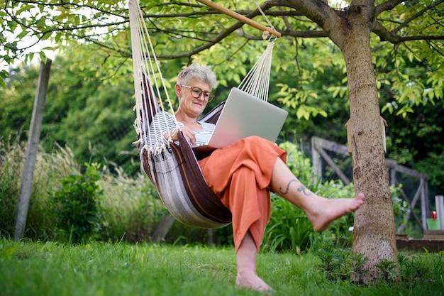 Портрет активной старшей женщины с ноутбуком, работающей на открытом воздухе в саду в гамаке
