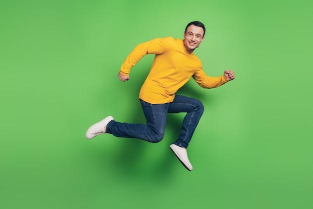 アクティブなスポーティーな男のジャンプランの肖像画は、緑の背景に急いで急いでください