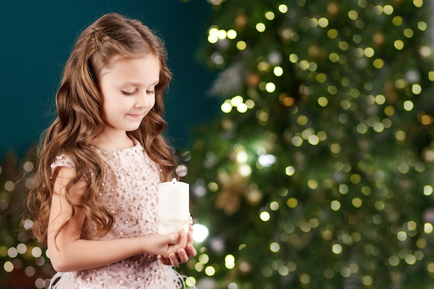 Портрет острой длинноволосой маленькой девочки в платье с огнями. маленькая девочка держит горящую свечу. рождество, новый год и концепция празднования дня рождения. зимние каникулы. копировать пространство