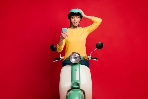 빨간 벽에 셀 흥분된 얼굴을 사용하여 오토바이에 앉아 중독 놀란 소녀의 초상화