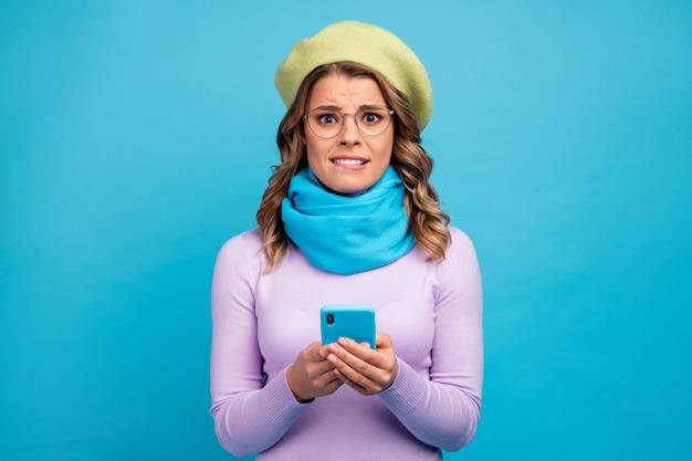 Портрет зависимой девушки-блогера, нервничающей по мобильному телефону на синей стене