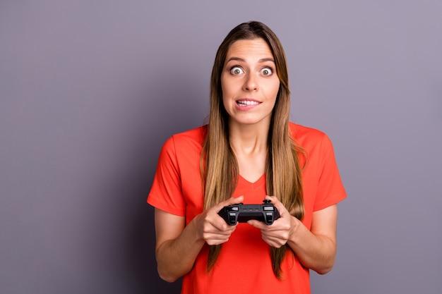 Портрет увлеченной геймерки в красной футболке, позирующей на фоне фиолетовой стены