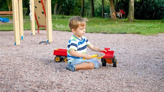 Портрет очаровательного 3-летнего мальчика малыша, играющего с игрушечным грузовиком с прицепом на детской площадке в парке. ребенок копает и строит из песка
