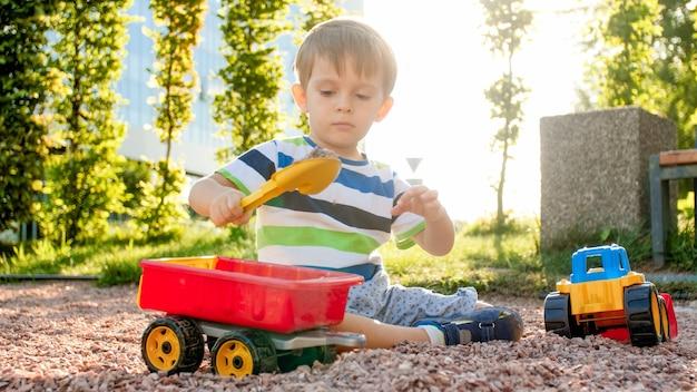 公園の遊び場でトレーラー付きのおもちゃのトラックで遊んでいる愛らしい3歳の幼児の少年の肖像画。砂から掘ったり作ったりする子供