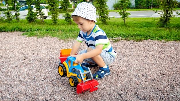 公園の遊び場でトレーラー付きのおもちゃのトラックで遊ぶ愛らしい 3 歳の幼児の少年の肖像画