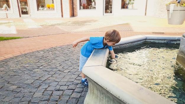 Портрет очаровательного 3-летнего мальчика, касающегося воды в фонтане в парке