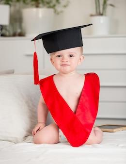 졸업 모자와 침대에 앉아 레드 칼라에 사랑스러운 아기 소년의 초상화