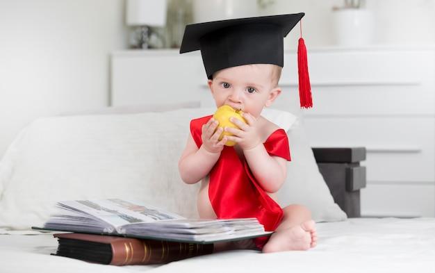 책에서 앉아서 사과 물고 졸업 모자에 사랑스러운 아기의 초상화. 더 현명하게 성장하는 아기의 개념