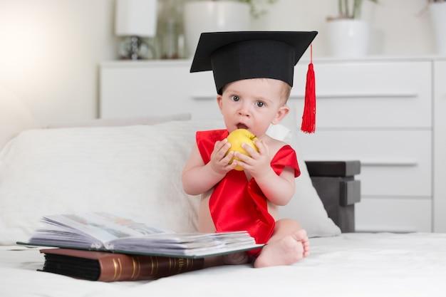 Портрет очаровательного мальчика в выпускной шапке, сидящего из книг и кусающего яблоко
