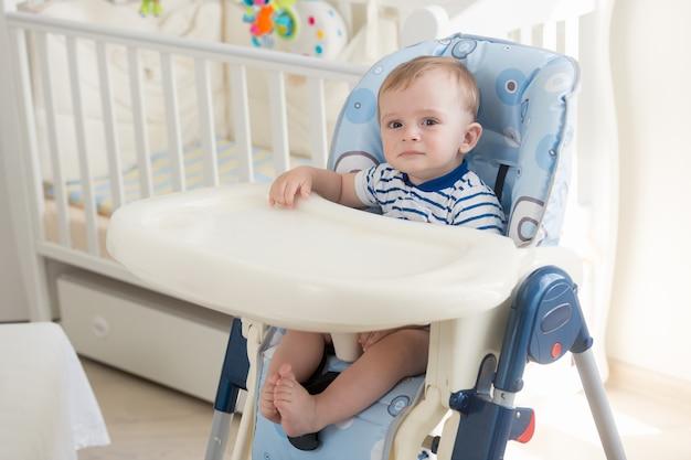 スプーンからフルーツソースを食べるエプロンで愛らしい赤ちゃんの肖像画