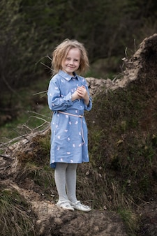 森の中に立ってカメラを見ている5歳の愛らしい白人の女の子の肖像画