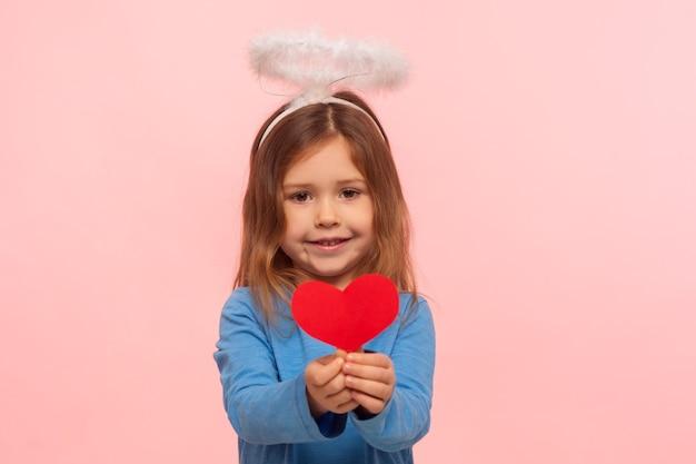 Портрет очаровательной милой дошкольной девочки с ангельским нимбом, держащим бумажное сердце и улыбающимся камере, маленькому купидону на день святого валентина, делящемуся любовью. закрытый студийный снимок изолирован на розовом фоне