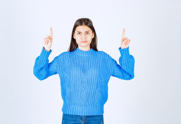 흰색에 가리키는 파란색 스웨터에 사랑스러운 여자의 초상화.