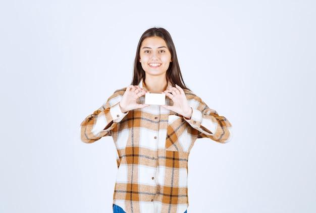 흰 벽에 명함을 보여주는 사랑스러운 소녀의 초상화.